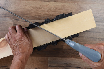High angle closeup of a woodworker using a miter box and hand saw to cut a board at an angle