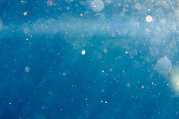 sunny blue underwater background with particles