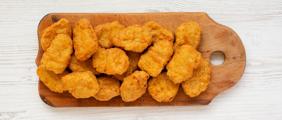 Chicken nuggets on a rustic wooden board on a white wooden surface, top view. Flat lay, from above, overhead.