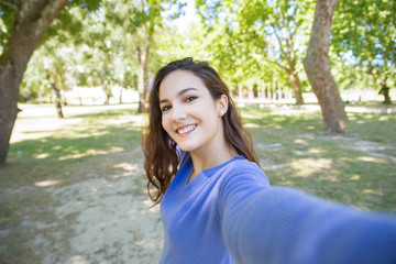 Happy young woman in blue sweater talking selfie in park. Carefree girl with wavy hair having fun alone in summer park. Environment concept