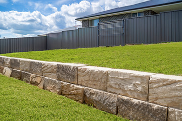 Stone retaining wall backyard green grass fence neighbour