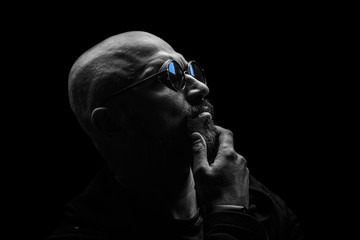 Pensive bald man with a gray beard in sunglasses on a dark background