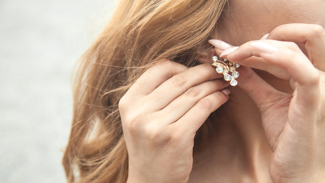 Woman putting on earrings. Dressing jewelry for a party