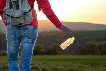 Plastic pollution environment. Hiker throwing away plastic bottle in nature.