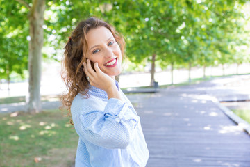 Joyful happy girl speaking on mobile phone in park. Beautiful young woman in casual speaking on...
