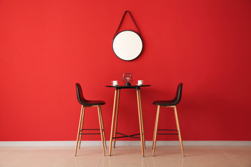 Table and chairs near color wall with mirror Wall mural