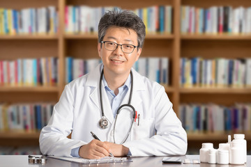 Asian male doctor sitting at desk smiling