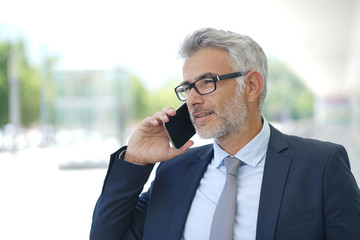 Mature businessman on cellphone outside contemporary office