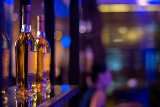 row of alcohol bottle on wooden shelf