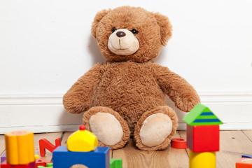 Teddybär und Holzbauklötze im Kinderzimmer