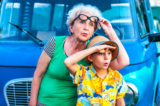 Trendy grandmothers with her grandson in beach colorful clothes near the retro car peer into the distance in surprise. Family summer vacation and travel concept