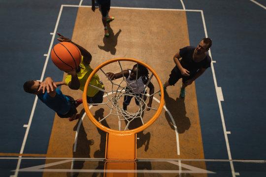 Basketball players playing basketball in basketball court