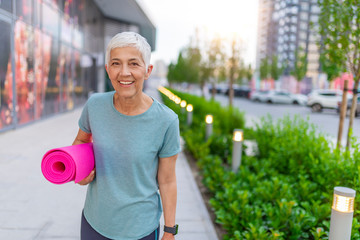 An elderly woman poses for a portrait after her workout. Senior woman walking with a yoga mat outside wearing sports wear and doing yoga. Gorgeous senior woman carrying a yoga mat outdoors and smiling