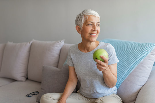 An aple a day keeps doctor away. Close up of a cheerful elderly woman eating an apple while smiling in the livingroom. Healthy mid age woman holding apple closeup