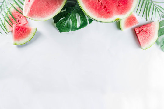 Creative watermelon layout. Summer trendy bright pattern with sliced watermelon and tropical leaves, Above, flatlay with copy space