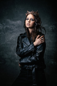 Young woman wearing a crown, a leather jacket, a hand on the shoulder