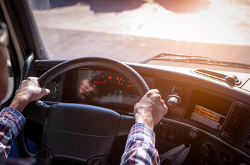 Truck driver keeps driving with one hands and change gears,The man Behind Semi Truck Steering Wheel,spot focus. Wall mural