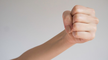 Woman's fist isolated on a light gray background. Close up to the camera.