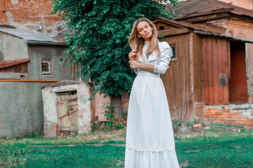 A lonely girl in a white vintage dress stands on the background of an old house