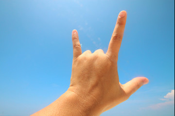 Hand sign of love and showing fingers means I love you on blue sky with sunlight and copty space.