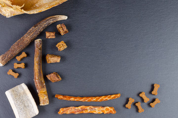 different dog food and snack, chicken filet, antlers, lung, ear on black background
