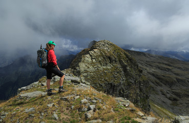 Fotomurales - Female hiker on a narrow ridge looking at the mountains in Ticino, Switzerland.
