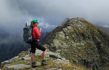 Fotomurales - Female hiker on a narrow ridge in the mountains. Via Alta Verzasca, Switzerland.