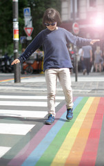 Young careful child walking through the rainbow crosswalk, halo effect