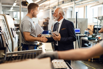 Young manual worker greeting senior manager in industrial building.