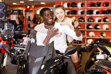 Happy  young couple satisfied with choice in modern motorcycle salon