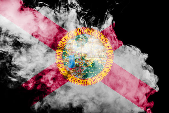 The national flag of the US state Florida in against a gray smoke on the day of independence in different colors of blue red and yellow. Political and religious disputes, customs and delivery.