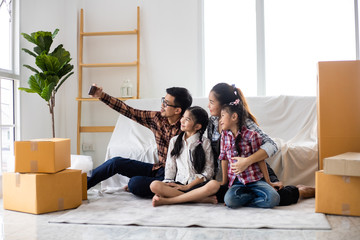 Asian couple husband and wife just moveing to new house and selfie together with smartphone happy and smile face in white living room
