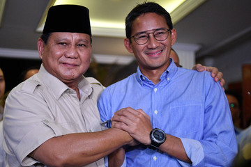 Indonesia's presidential candidate Prabowo Subianto shakes hands with his running mate Sandiaga Uno in Jakarta
