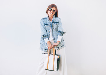 Wall Mural - Woman dressed elegant outfit with oversize denim jacket and shopper bag. Modern fashion outfit concept image.