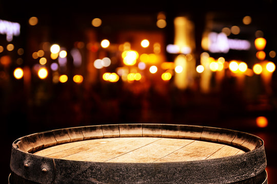 background of wooden barrel in front of abstract blurred restaurant lights