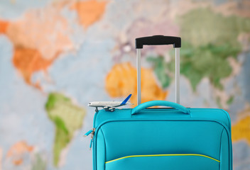 Wall Mural - holidays. travel concept. blue suitcase and airplane toy infront of world map background