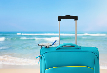 Wall Mural - holidays. travel concept. blue suitcase and airplane toy infront of tropical sea background