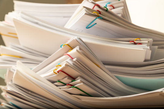 Stack of document paper with colorful paperclip.