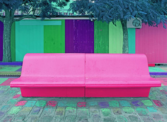 Pop art  styled concrete bench in vivid pink color with blue color tree and colorful wooden wall in background