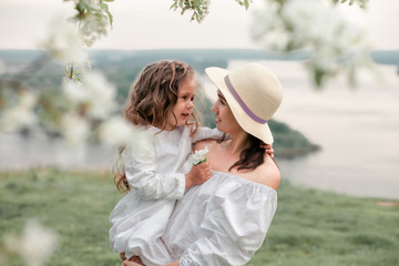 Mother hugs her daughter near the blossoming apple trees. Happy family outdoors