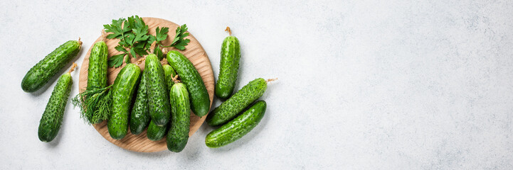 Fresh cucumbers on wooden cutting board and kitchen table