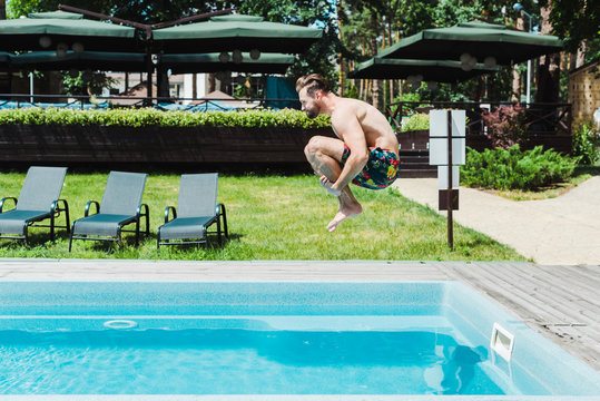 side view of bearded man with barefoot jumping in swimming pool