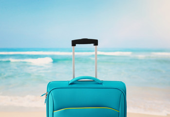 Wall Mural - holidays. travel concept. blue suitcase infront of tropical background
