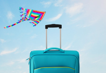 Wall Mural - holidays. travel concept. blue suitcase infront of blue sky with kite background