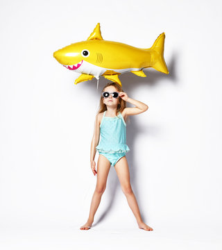 positive little girl dressed in a swimsuit, wears a balloon in the shape of a yellow shark fish