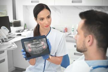 Female dentist showing teeth x-ray on tablet