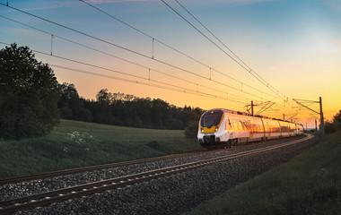 Poster Gris traffic Modern German train traveling at sunset