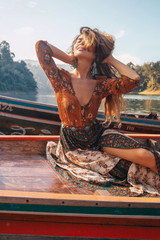 Acrylic Prints Brown fashionable young model in boho style dress on boat at the lake