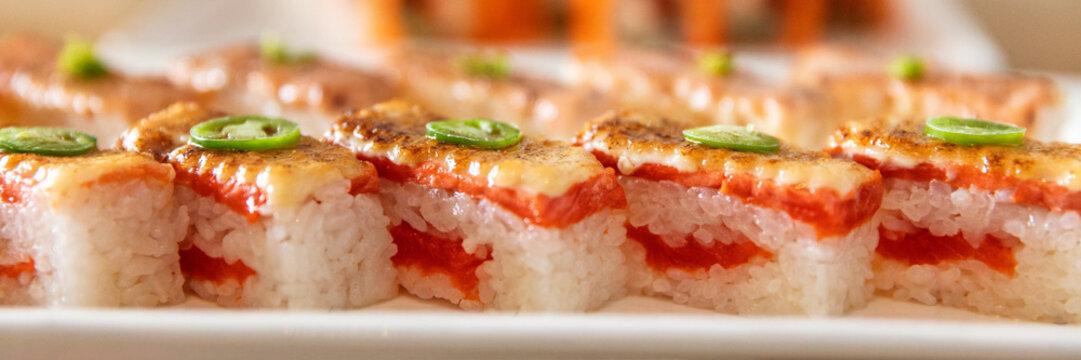 Japanese restaurant food banner panoramic closeup of sushi plate presentation background. Closeup of Aburi Oshi sushi, seared salmon box pressed vinegar rice, Osaka region, Japan travel. Header crop.
