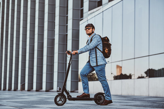 Cheerful modern man is driving his electro scooter near his office after long hard day.